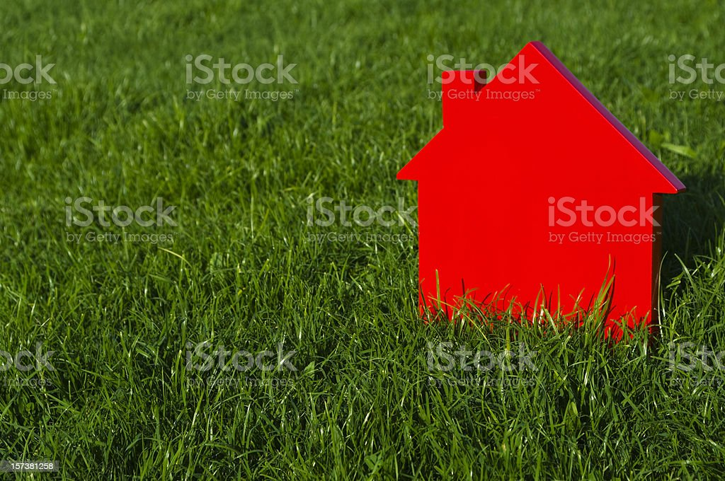 Red model house on green grass royalty-free stock photo