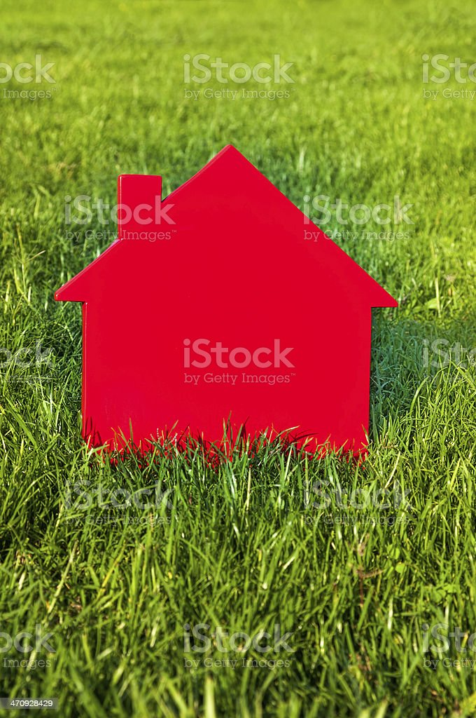 Red model house on green grass stock photo
