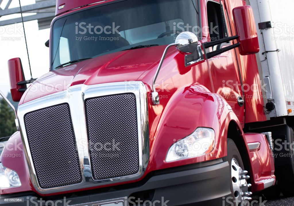 Red modern big rig semi truck with shiny grille and painted surface run on the road stock photo