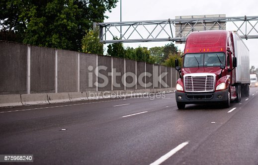 Red modern reliable American big rig semi truck with dry van semi trailer running on wide highway with concrete fens in raining weather