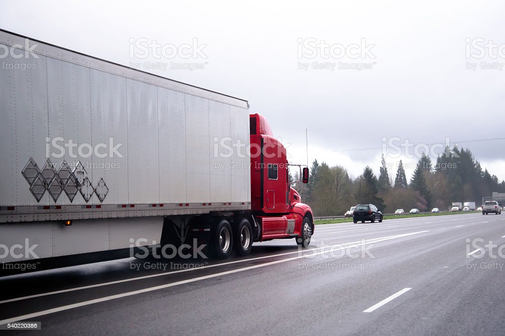 Red modern semi truck transporting cargo trailer on highway stock photo