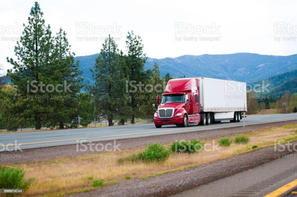 Red modern semi truck with dry van trailer moving by divided highway I-5 in California stock photo