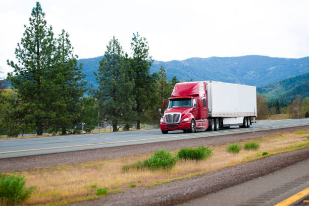 Red modern semi truck with dry van trailer moving by divided highway I-5 in California - foto stock