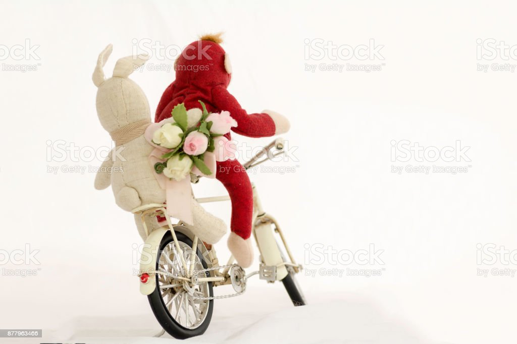 Red monkey doll with white rabbit doll and pink roses bouquet  riding a bike, on a white background. stock photo