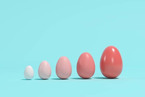 Rote Monotone Eier in verschiedenen Größen auf blauem Hintergrund. Minimale Osteridee. – Foto