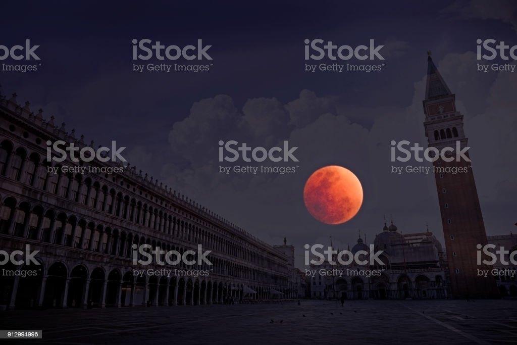 Rode maan in blauwe uur over Venetië Italië foto
