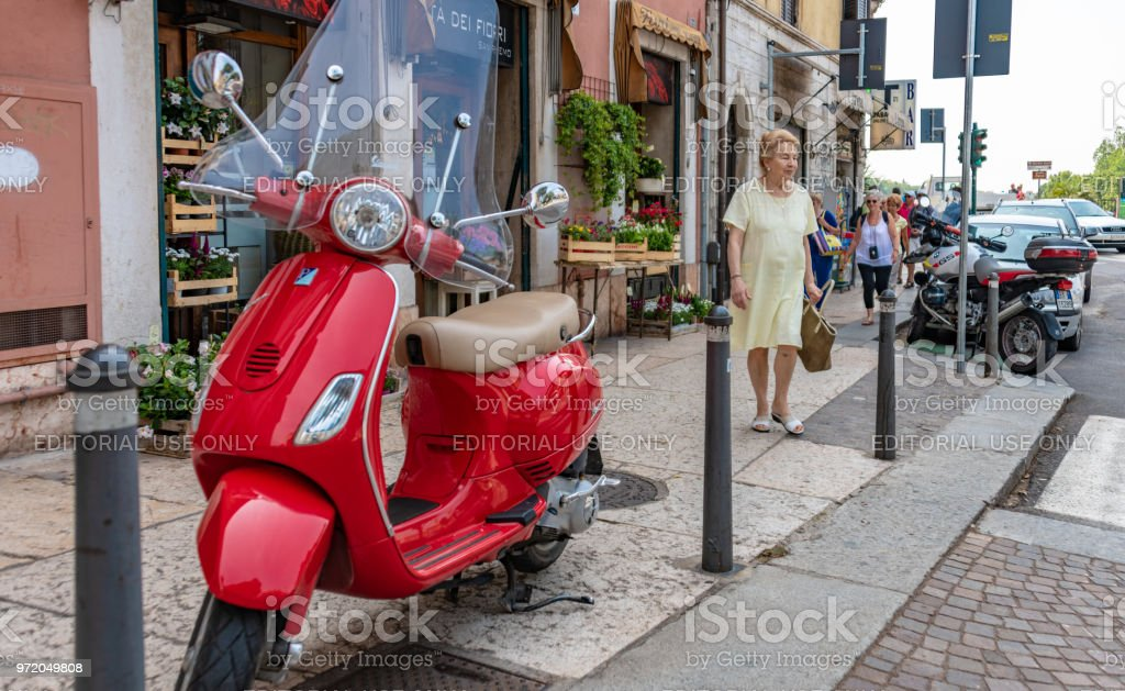 Red moped and senior lady in Verona, Italy stock photo