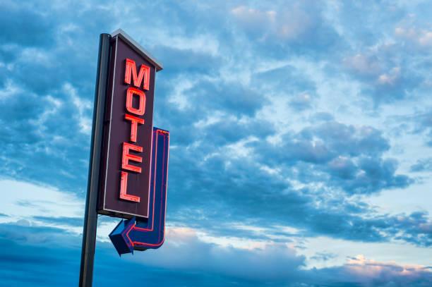 czerwony motel neon znak nad zachodem słońca pochmurne niebo - motel zdjęcia i obrazy z banku zdjęć
