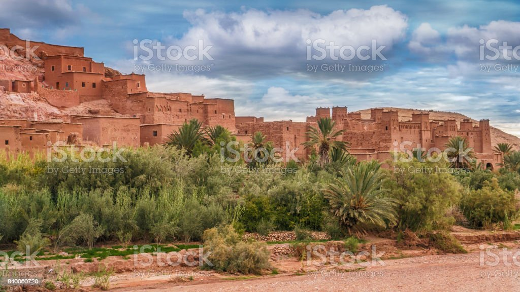 Red mud brick walls of Ksar Aitbenhaddou, ancient fortress in Morocco. Date palm trees in foreground. stock photo