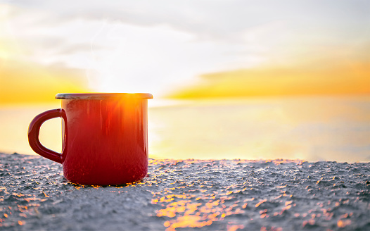 Good morning sunrise concept. Red mug with tea or coffee on the beach with sea on background. Sunlight and sunrise. Lets start a new day. Space for text