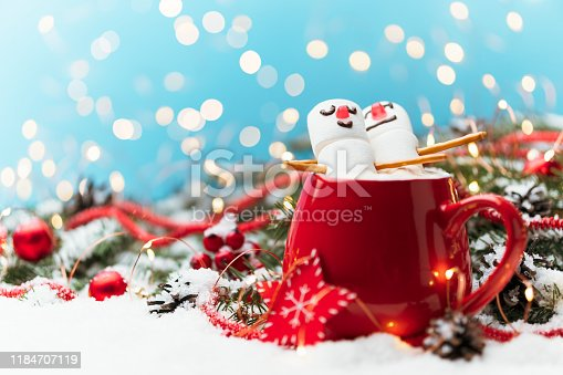 istock Red mug with hot chocolate and two marshmallows in love. Christmas meeting a couple in love concept. 1184707119