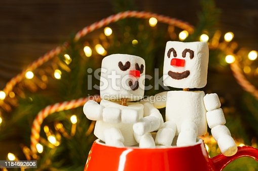 istock Red mug with hot chocolate and two snowmen in love made from marshmallows. Christmas and New Year composition. 1184692606