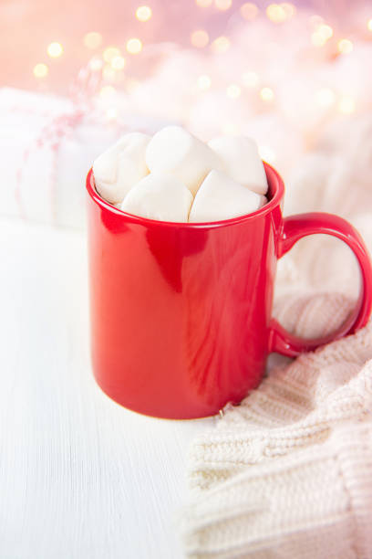 rote tasse mit heißer schokolade kakao trinken und marshmallows an der spitze. glitzernde lichter garland im hintergrund. strickpullover-geschenk-box. weiche pastellfarben. weihnachten silvester romantisch gemütlich - strickmantel stock-fotos und bilder