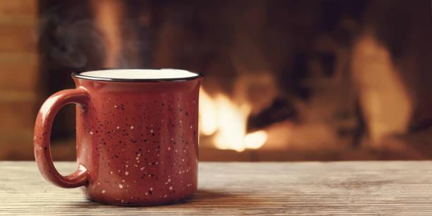 Roter Becher mit heißem Tee vor einem brennenden Kamin, Komfort, Winterurlaub und Wärme des Herdkonzepts – Foto