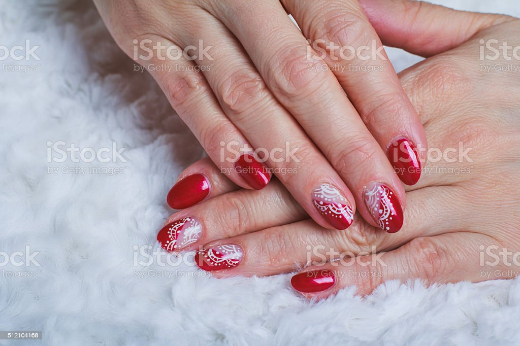 Red Nail Art With White Lace With Dots And Lines stock photo | iStock