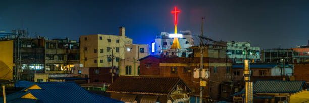 Red neon crucifix shining brightly over city rooftops panorama Seoul stock photo