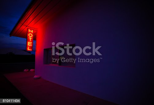A red, neon Hotel sign illuminates the side of a wall in Marfa, Texas.