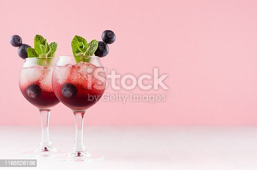 Red north homemade liquors in two wineglasses with ice cubes, blueberry, green mint on soft pastel pink background and white wood table, copy space.