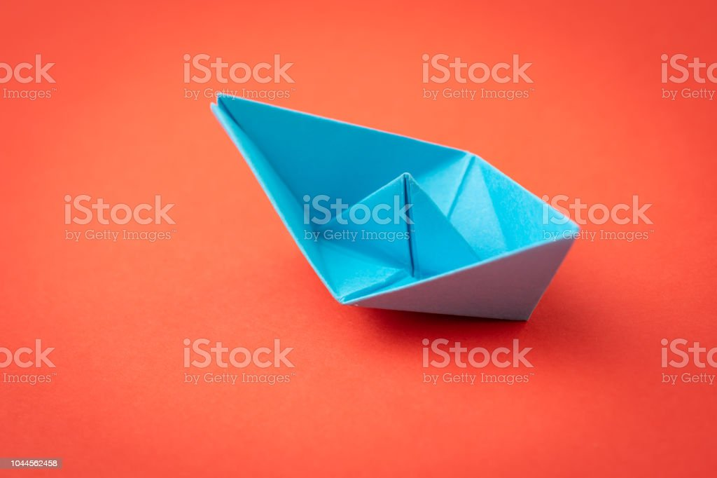 Red ocean business competition, survive success or winner company metaphor concept, blue origami paper ship on red background as ocean in minimal style stock photo