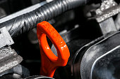 istock Red oil dipstick in car engine. Measuring level of engine oil. Dipstick oil level gauge with red color for Checking engine oil level of engine system. 1196990727