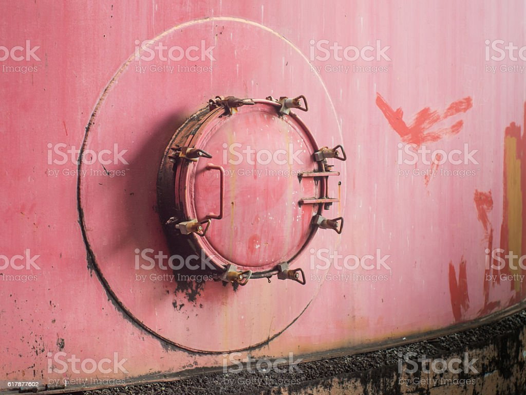 Red old and rusty manhole of storage tank. stock photo