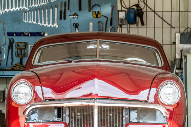 red oldtimer in a car repair shop in process in front of a wall with screw-wreches