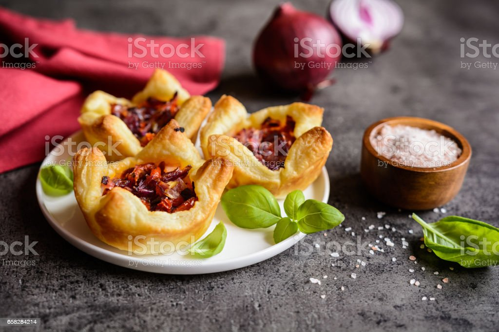 Red onion and sun-dried tomato mini tartlets stock photo