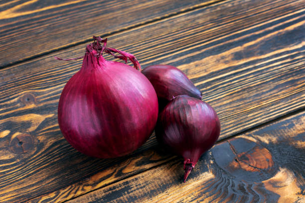 Red onion on wooden background. Red onion close up on brown wooden background. One large onion, two smaller ones. spanish onion stock pictures, royalty-free photos & images