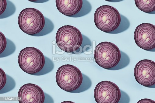 Half sliced red Spanish onion in a row on blue background