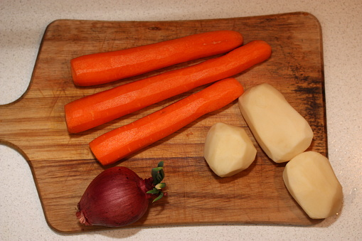 Red onion, peeled potatoes and carrots on the dirty chopping board. Top view.