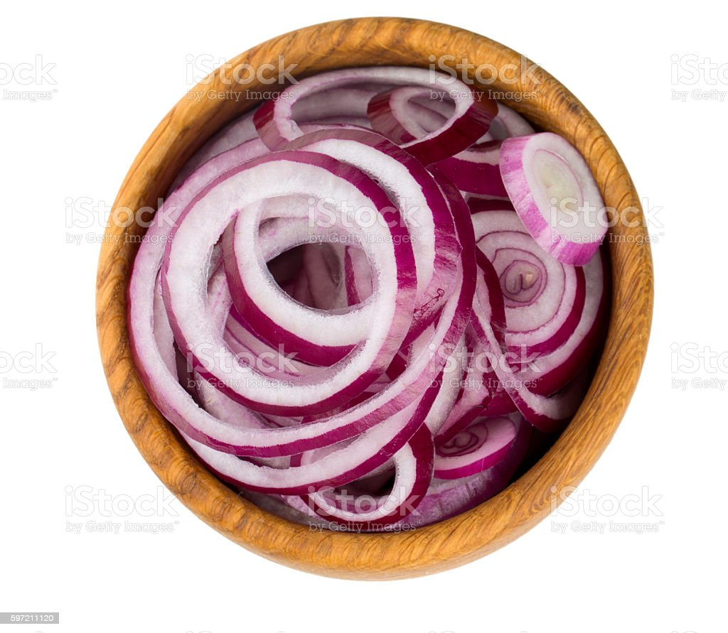 red onion slices in a wooden bowl isolated on white stock photo