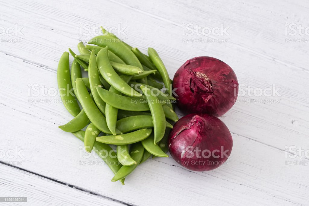 Two Red Scottish Grown Onions and a pile of green sugar snap peas on...