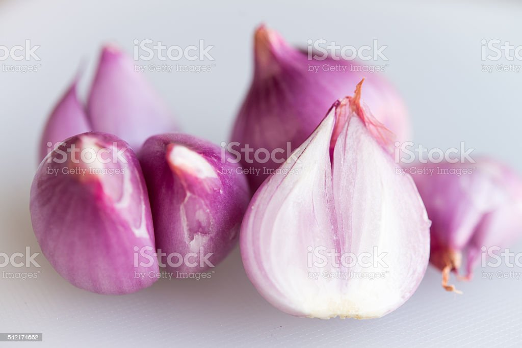 Red onions on a plastic chopping board stock photo