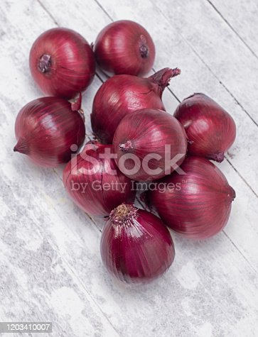 Red onions on wood background