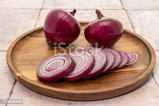 Red onions with slices on a wood plate background