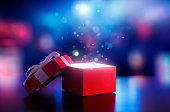 istock Red open gift box with magical light against blurred bokeh light background 1162271564