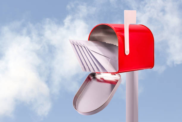 Red open mailbox with five white envelopes and sky background stock photo