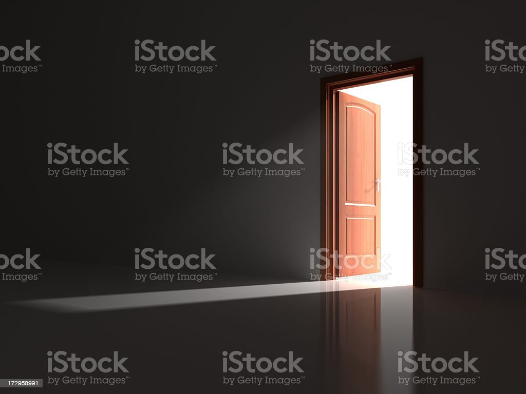 A red opened door letting light into a dark room stock photo