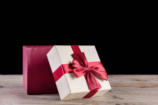 red opened gift box with bow on retro wooden desk - puste pudełko zdjęcia i obrazy z banku zdjęć