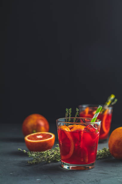 Red orange juice in a large glass or blood orange sparkling vodka cocktail or aperitif with campari stock photo