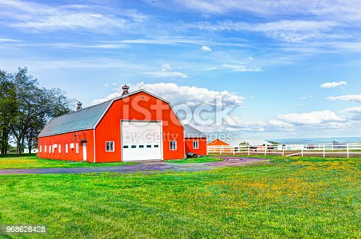 Red orange painted barn shed with white doors in summer landscape field in countryside