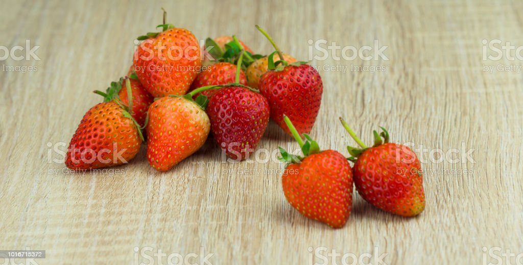 Red, Orange strawberry on the wooden background stock photo