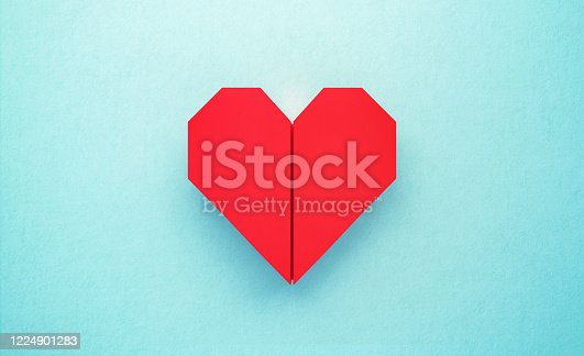 Red origami heart on turquoise background. Horizontal composition with copy space. Love concept.