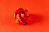 Red origami rose on red background. Japanese art of paper folding. Flat square sheet of paper transferred into a finished sculpture through folding and sculpting. Close up. Macro photo.