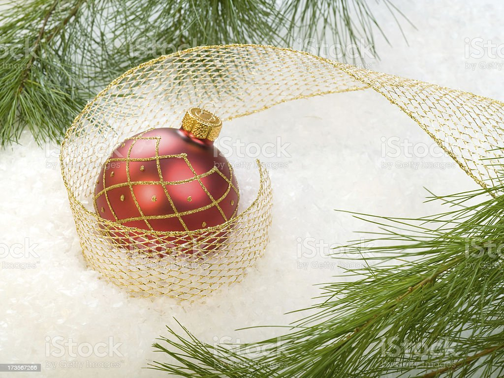 Red ornament with gold ribbon and evergreens stock photo