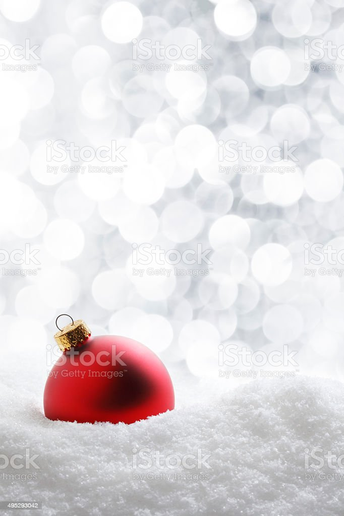 Red Ornaments on Snow With Blurred White Lights In Background stock photo