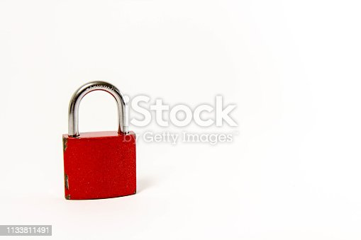 Photo of red closed padlock closeup on white background