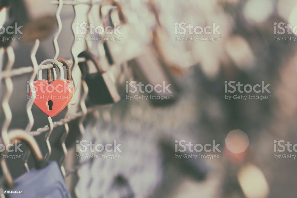 Red padlock, heart shape, clipped to a wire mesh stock photo
