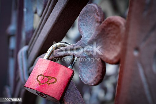 Red heart padlock with two hearts locked on fence.