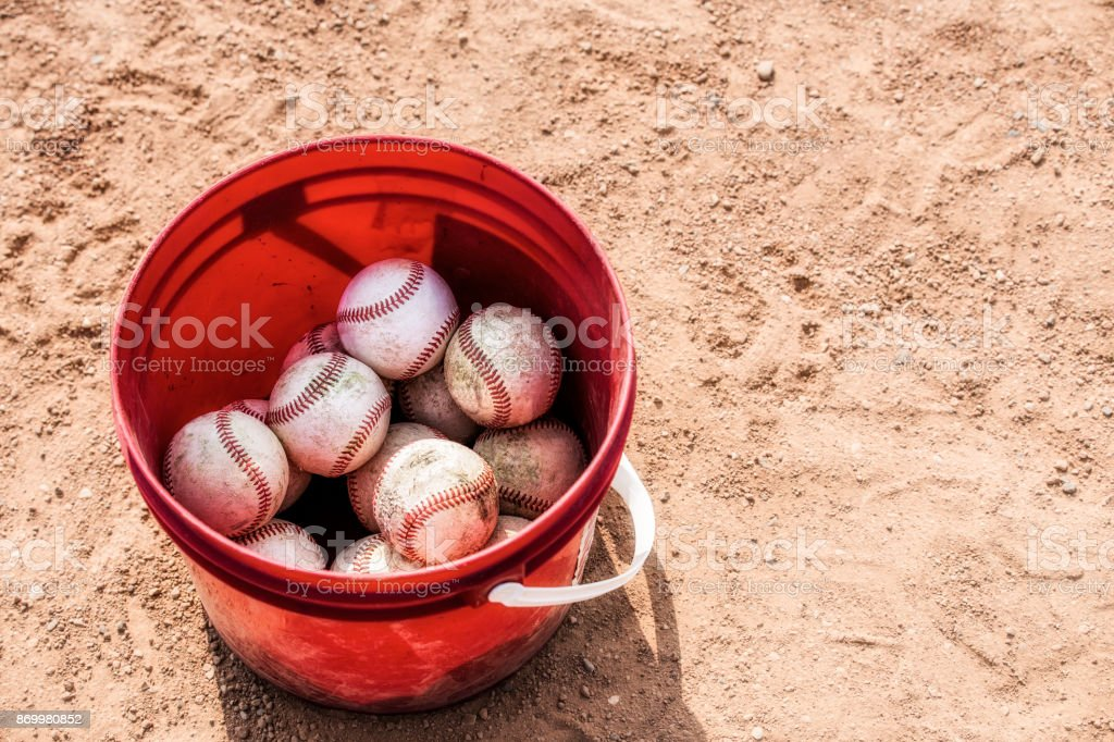 Red pail of baseballs stock photo